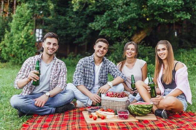 Eine gruppe von freunden hat spaß. fröhliche mädchen und männer verbringen das wochenende im freien beim picknick im park Premium Fotos