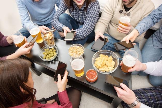 Eine gruppe von freunden macht zu hause einen aperitif mit snacks und bier Premium Fotos