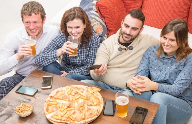 Eine gruppe von freunden trinkt bier, isst pizza, redet und lächelt, während sie sich zu hause ausruhen Premium Fotos
