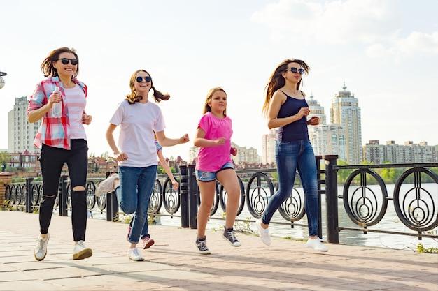 Eine gruppe von müttern und töchtern laufen auf der straße im park Premium Fotos