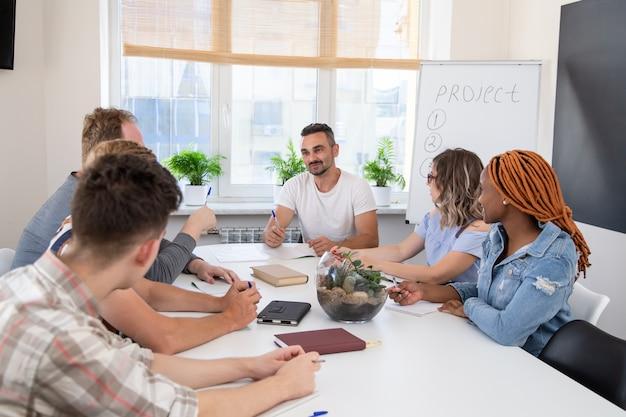 Eine gruppe von personen bei einem geschäftstraining hört dem sprecher zu. teamarbeit in einem internationalen unternehmen Premium Fotos