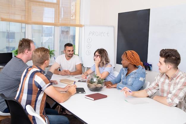 Eine gruppe von studenten bei einem geschäftstraining hört dem sprecher zu. Premium Fotos