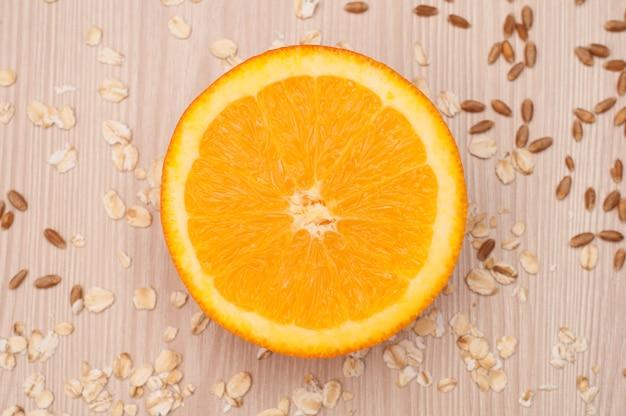 Eine halbe orange auf der tischnahaufnahme mit haferflocken und weizen auf hintergrund Premium Fotos
