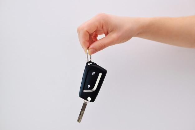 Eine hand, die einen autoschlüssel auf einem weißen hintergrund hält. Premium Fotos