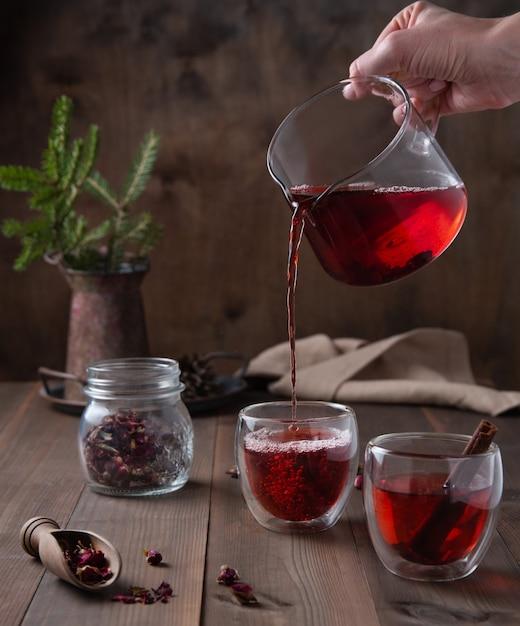 Eine hand gießt roten rosentee aus einer glasteekanne in klare tassen auf einem braunen holztisch. vorderansicht Premium Fotos