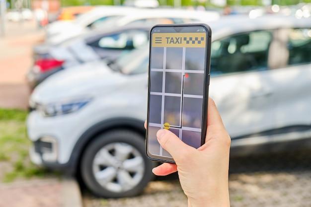 Eine hand hält ein smartphone mit einer taxi-anwendung, die die bewegung zum ort zeigt Premium Fotos