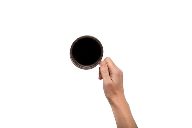 Eine hand hält eine tasse mit heißem kaffee auf einem weißen isolierten hintergrund. frühstückskonzept mit kaffee oder tee. guten morgen, nacht, schlaflosigkeit. flache lage, draufsicht Premium Fotos