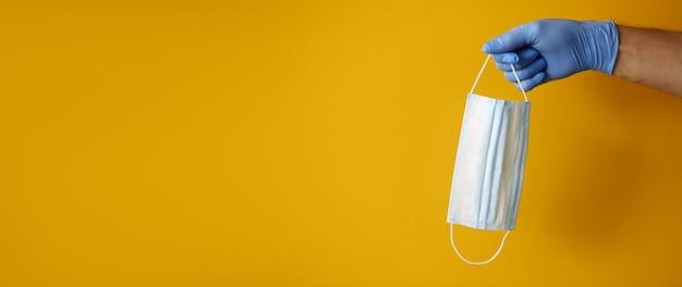 Eine hand in einem gummihandschuh hält eine schutzmaske auf einem gelben hintergrund. konzept des schutzes gegen alle arten von mikroben und viren Premium Fotos