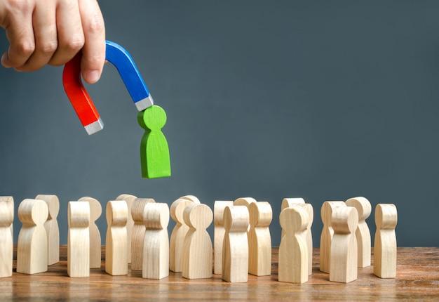 Eine hand mit einem magneten zieht eine grüne menschliche figur aus der großen menschenmenge heraus. neue arbeitskräfte einstellen Premium Fotos