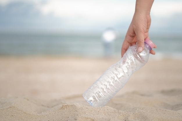Eine hand nimmt die plastikflasche vom strand Premium Fotos