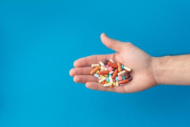 Eine handvoll farbiger pillen auf der handfläche. medizinisches konzept. einkaufen in der apotheke. Premium Fotos