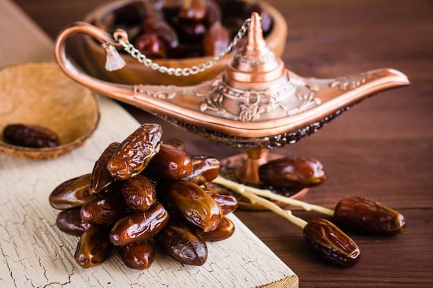 Eine handvoll getrocknete dattelfrüchte auf einer lampe von aladdin. frische orientalische süßigkeiten. Premium Fotos