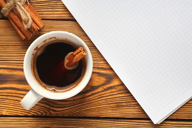 Eine haufen zimt mit einem seil, einer tasse kaffee und einem notizbuch gestrickt Premium Fotos