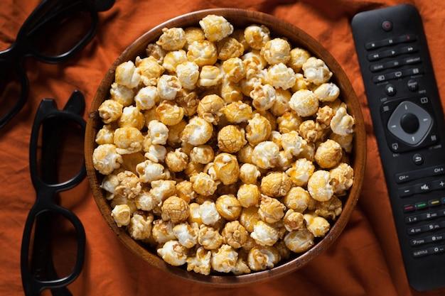 Eine hölzerne schüssel popcorn und fernbedienung. Premium Fotos