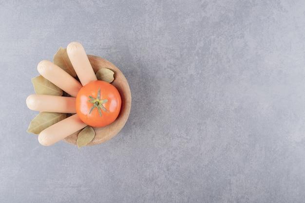 Eine holzschale mit gekochten würstchen mit roten tomaten und lorbeerblättern. Kostenlose Fotos