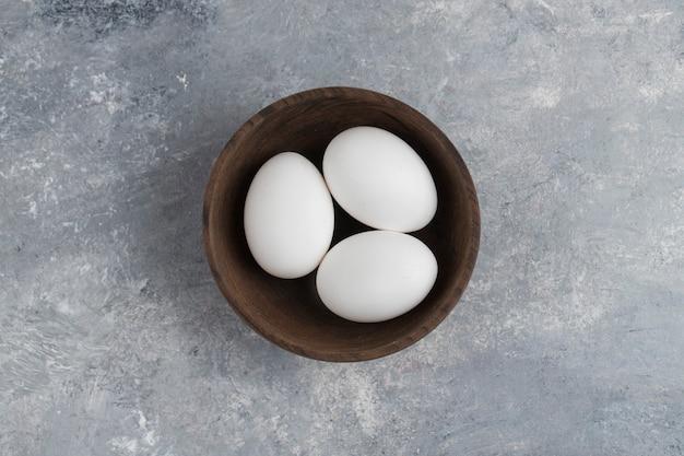 Eine holzschale voller frischer weißer hühnereier auf einem marmorhintergrund. Kostenlose Fotos