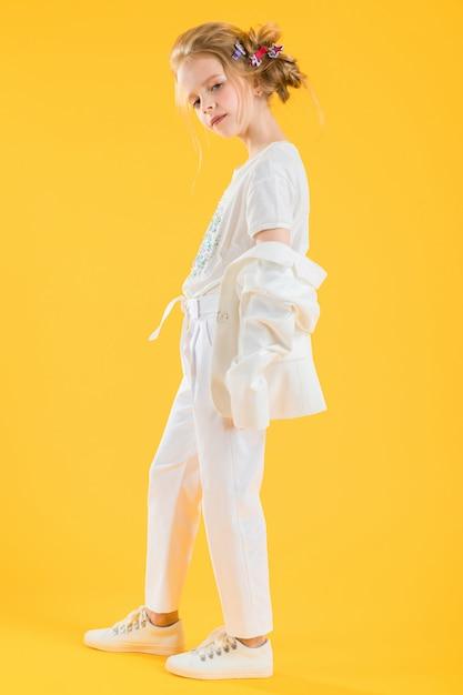 Eine jugendliche in der weißen kleidung, die auf gelb aufwirft Premium Fotos