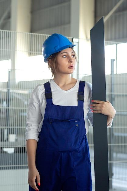 Eine junge attraktive dame der vorderansicht im blauen bauanzug und im helm, die das schwere metallische detail während des architekturbaus der tagesgebäude halten Kostenlose Fotos