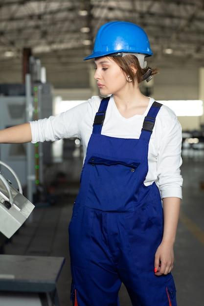 Eine junge attraktive dame der vorderansicht im blauen bauanzug und in den helm, die maschinen im hangar steuern, der im bereich gebäudearchitekturbau arbeitet Kostenlose Fotos