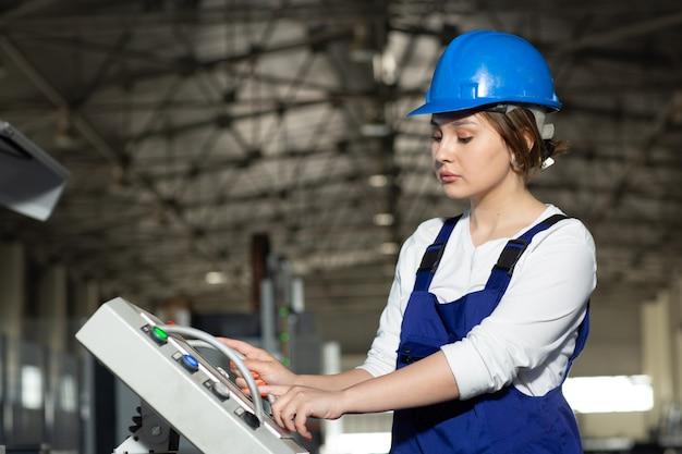 Eine junge attraktive dame der vorderansicht im blauen bauanzug und in den helm, die maschinen im hangar steuern, die während der architektur des tagesgebäudes arbeiten Kostenlose Fotos