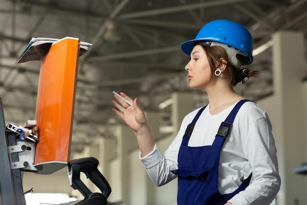 Eine junge attraktive dame der vorderansicht im blauen bauanzug und in den helm, die maschinen im hangar während des architekturbaus der tagesgebäude steuern Kostenlose Fotos