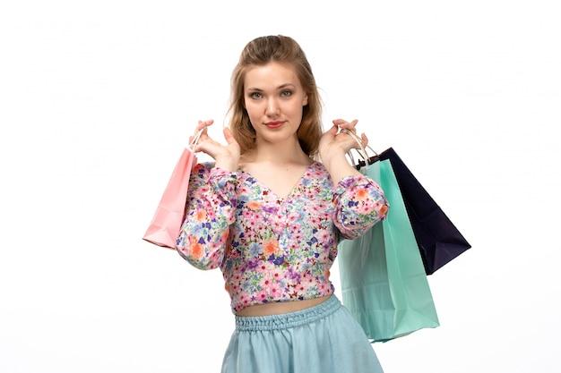 Eine junge attraktive dame der vorderansicht im bunten blumenentwurfshemd und im blauen rock, die einkaufspakete auf dem weiß halten Kostenlose Fotos