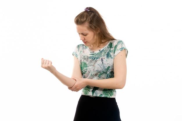 Eine junge attraktive dame der vorderansicht im entworfenen hemd und in der schwarzen hose, die unter armschmerzen auf dem weiß leiden Kostenlose Fotos