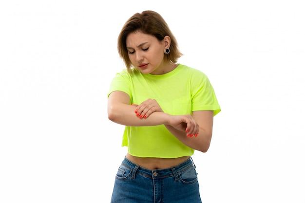 Eine junge attraktive dame der vorderansicht im grünen hemd und in den blauen jeans, die unter handschmerz auf dem weiß leiden Kostenlose Fotos