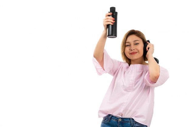 Eine junge attraktive dame der vorderansicht im rosa hemd und in den blauen jeans mit den schwarzen kopfhörern, die schwarze thermoskopf-schwarze ohrhörer trinken, die auf dem weiß lächeln Kostenlose Fotos