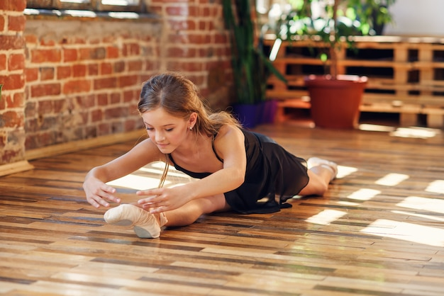 Eine junge ballerina, die im tanzsaal schnur macht. Premium Fotos