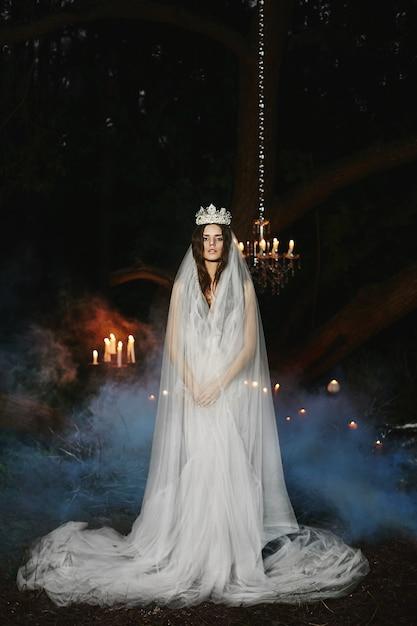 Eine junge braut mit einer krone und einem schleier auf dem kopf steht in einem wald und posiert im freien, märchenbild Premium Fotos