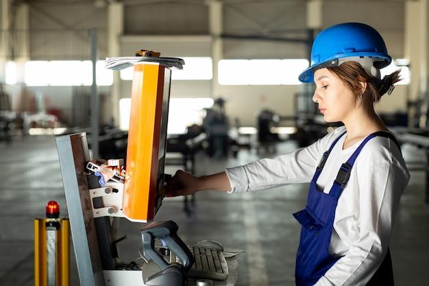 Eine junge dame der vorderansicht im blauen bauanzug und im helm, die maschinen im hangar während des architekturbaus der tagesgebäude steuern Kostenlose Fotos