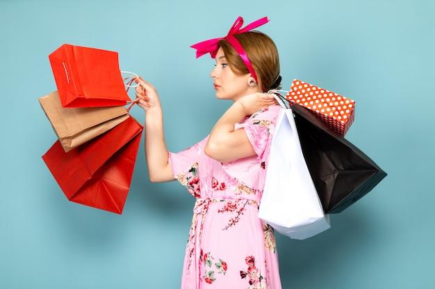Eine junge dame der vorderansicht in der blume entwarf rosa kleid, das einkaufspakete auf blau hält Kostenlose Fotos