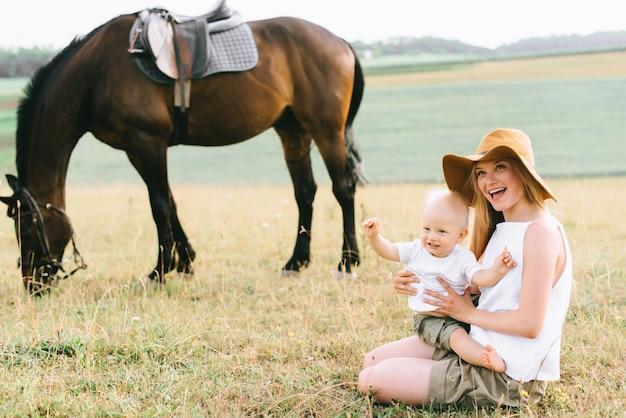 Eine junge familie hat spaß auf dem feld. eltern und kind mit einem pferd Premium Fotos