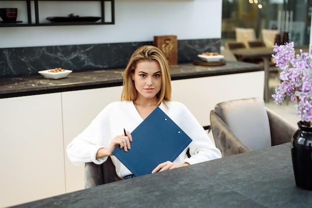 Eine junge frau arbeitet in ihrer küche und schreibt etwas in ein notizbuch. geschäftsfrau arbeitet von zu hause aus. Premium Fotos