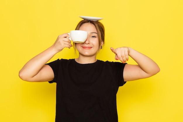 Eine junge frau der vorderansicht im schwarzen kleid, das kaffee trinkt und auf gelb lächelt Kostenlose Fotos