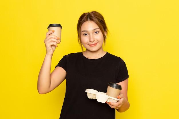 Eine junge frau der vorderansicht im schwarzen kleid, die kaffeetassen mit lächeln auf ihrem gesicht auf gelb hält Kostenlose Fotos