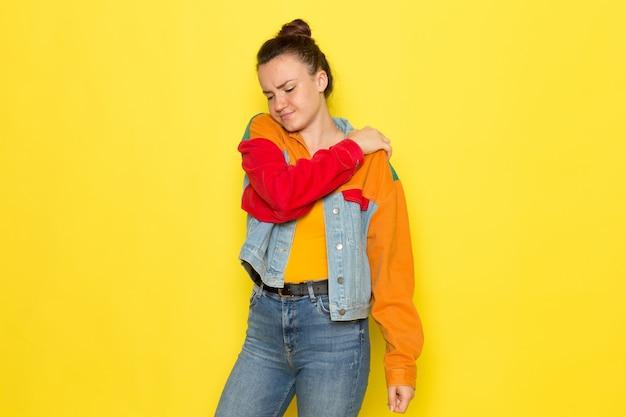 Eine junge frau der vorderansicht in der bunten jacke des gelben hemdes und der blauen jeans, die einen rückenschmerz haben Kostenlose Fotos