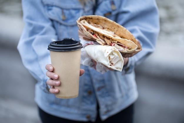 Eine junge frau, die ein glas kaffee und fast food hält Kostenlose Fotos