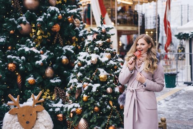 Eine junge frau geht zu weihnachten auf dem platz in der nähe der geschmückten weihnachtsbäume. candy ist ein lutscher in form eines herzens. Premium Fotos