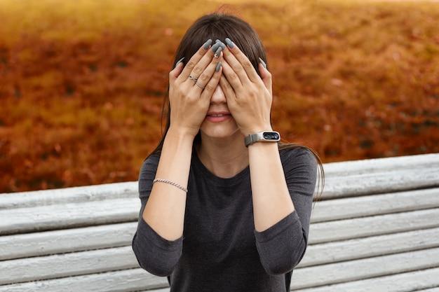 Eine junge frau im park bedeckte ihr gesicht mit den händen Premium Fotos