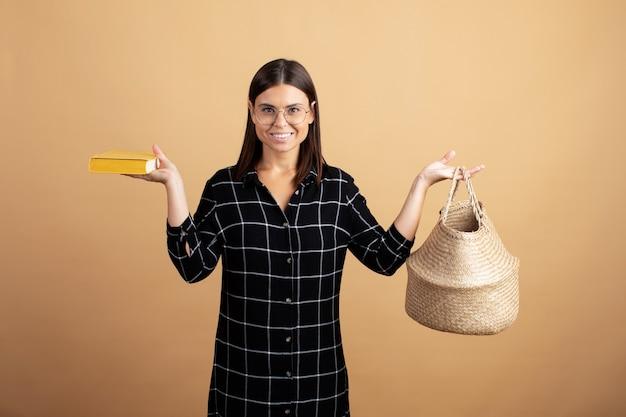 Eine junge frau in einem karierten kleid steht mit einer weidentasche auf einem orangefarbenen hintergrund Premium Fotos