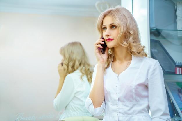 Eine junge frau in einer weißen robe, die um das telefon im büro eines kosmetikers ersucht. Premium Fotos