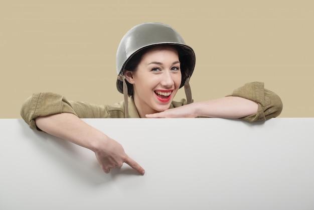 Eine junge frau kleidete in der amerikanischen militäruniform ww2 an, die leeres leeres schild zeigt Premium Fotos
