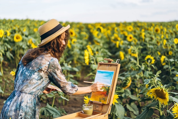 Eine junge frau mit lockigem haar und hut malt in der natur. eine frau steht in einem sonnenblumenfeld an einem schönen tag Premium Fotos