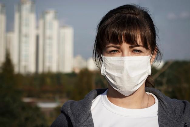 Eine junge frau mit maske in der stadt, konzept der luftverschmutzung Premium Fotos