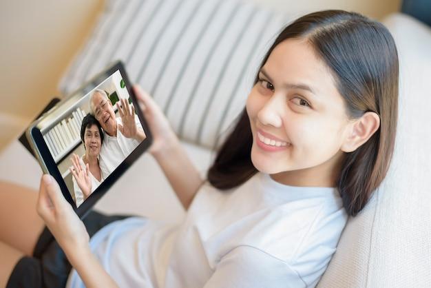Eine junge frau nutzt tablet für videoanrufe oder webcam für großeltern, telekommunikationstechnologie und elternschaftsfamilienkonzept. Premium Fotos