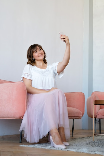 Eine junge frau sitzt auf der couch im zimmer und macht ein selfie am telefon Premium Fotos