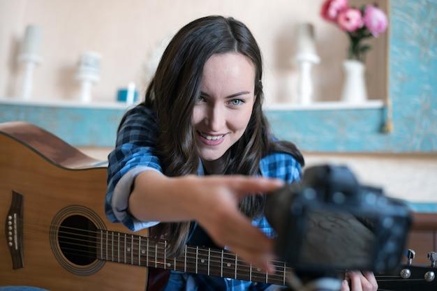 Eine junge frau stellt die kamera scharf, um ein musikblog mit gitarre aufzunehmen Premium Fotos