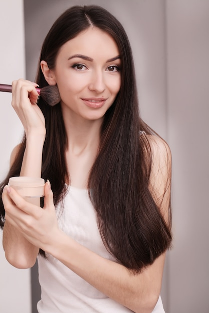 Eine junge frau trug mit einem pinsel flüssige grundierung auf ihr gesicht auf Premium Fotos